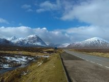 Snow capped mountains of Glencoe. Snow capped mountains Glencoe seen from Rannoch Moor shine in the winter sun as more snow clouds are blown in royalty free stock photo