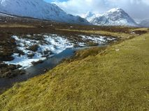 Snow capped mountains of Glencoe stand proud under breaking winter blue skies as low lying snow melts into the river. Snow capped mountains Glencoe stand proud stock images