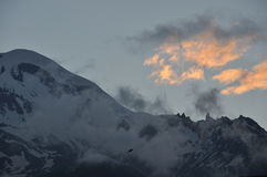 Snow-capped mountains Kazbek at dawn and the valley below where there is a church siete Trinity. Royalty Free Stock Image