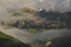Snow-capped mountains Kazbek at dawn and the valley below where there is a church siete Trinity Royalty Free Stock Photo