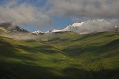 Snow-capped mountains Kazbek at dawn and the valley below where there is a church siete Trinity Royalty Free Stock Image