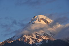 Snow-capped mountains Kazbek at dawn and the valley below where there is a church siete Trinity. Stock Photography