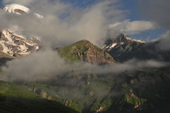 Snow-capped mountains Kazbek at dawn and the valley below where there is a church siete Trinity. Royalty Free Stock Images