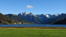 Snow capped mountains, lake and green meadow Stock Photos