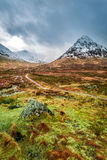 Snow capped mountains and a path in Glencoe Stock Photography
