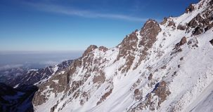 Snow-capped mountains. Shooting with the drone. White snow on gray and brown stones. stock video