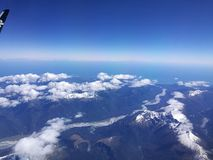 Snow-capped Mountains from Sky, Blue. Clouds, snow, mountains, bright blue Royalty Free Stock Images