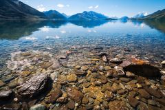 Snow capped mountains view in summer from the rocky shore of lake Wakatipu. Low angle view at Lake Wakatipu with snow capped mountains and Pig and Pigeon Islands Royalty Free Stock Images