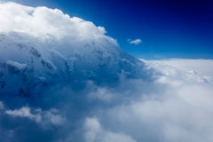Snow capped peak rising amidst  clouds Stock Photography