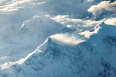 Snow-capped peaks of mountains in the clouds. Royalty Free Stock Photo