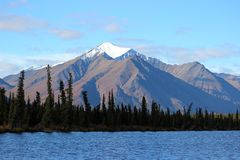 SNOW CAPPED ROCKY MOUNTAIN BLUE LAKE FORREST AND BLUE SKY Stock Photo