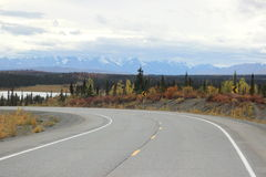 SNOW CAPPED ROCKY MOUNTAINS FALL FORREST AND CURVED HIGHWAY Stock Photos