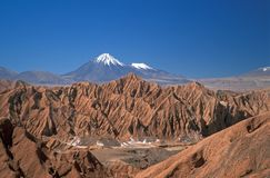 Snow Capped Volcano. Natural rock formations of the Atacama Desert and beyond the snow capped peaks of the Western Cordilleras Royalty Free Stock Photography