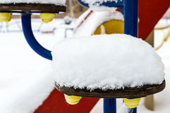 Snow caps on children`s swing. Close-up. Winter landscape Royalty Free Stock Photography