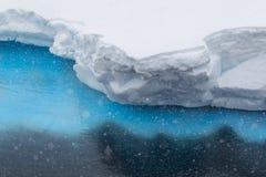 Snow falling on iceberg ledge Stock Photos