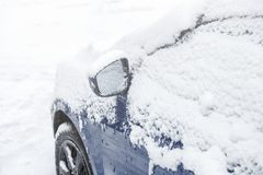 Snow on car wing mirror. Frozen car, blue car covered snow at winter day. Urban scene of city life in winter stock images