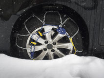 Snow chain on car tyre in snow Stock Photos