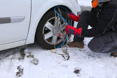Snow chains in the car tyre in winter on snow Royalty Free Stock Images