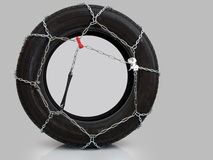 Snow chains on tyre, over grey. Unbranded chains. Stock Image
