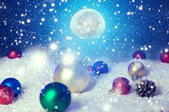 Snow christmas magic lights background. Christmas card with a winter forest and christmas decorations in a moonlit night. The royalty free stock photography