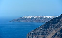 Snow City. On the way to the island of Santorini, a beautiful view over the city. In the blue expanse of the Mediterranean Sea, Black Mountain Island Stock Images