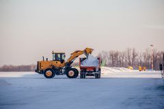 Snow cleaning in airport. Excavator loads snow into dump truck.  stock photos