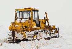 Snow cleaning with caterpillar Royalty Free Stock Images