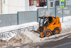 Snow cleaning pavements and streets of city which are covered in Stock Image