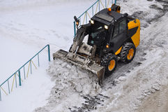 Snow cleaning on roads by means of special equipment. Royalty Free Stock Photo