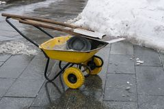 Snow cleaning tools - wheelbarrow, bucket and shovel Stock Photo