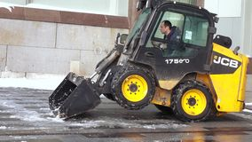Snow cleaning tractor. MOSCOW, RUSSIA - FEBRUARY 09, 2018: Tractor cleaning up the street after the night snowfall in February 2018 in Moscow Russian Federation stock footage
