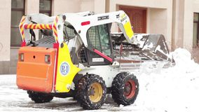 Snow cleaning tractor. MOSCOW, RUSSIA - NOVEMBER 25, 2017: Tractor cleaning up the street after the night snowfall stock footage