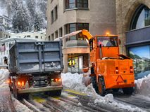 Snow cleaning tractor snow-removal machine loading pile of snow on a dump truck. Snow plow outdoors cleaning street city after. Blizzard or snowfall royalty free stock images