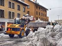 Snow cleaning tractor snow-removal machine loading pile of snow on a dump truck. Snow plow outdoors cleaning street city after. Blizzard or snowfall stock photo