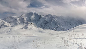Snow cliffs. Panoramic view on mountains in winter Stock Image
