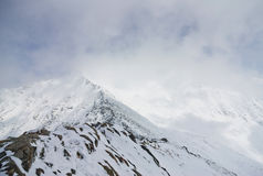 Snow cloud covers the mountain peaks and trees Royalty Free Stock Photography