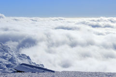 Snow clouds below. Aerial View of a Cloudscape and barren mountains below Stock Photo