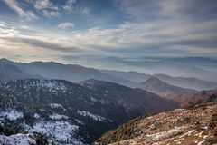 Snow clouds and layers of mountains royalty free stock photo