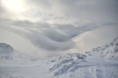 Snow and clouds. View on clouds from mountain path stock photos