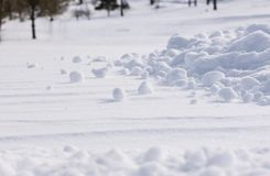 Snow Clumps Scattered. Close view of several clumps of snow in various shapes scattered out across a snow covered landscape royalty free stock photography
