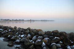 Snow coated stone pier after sunset Stock Photos