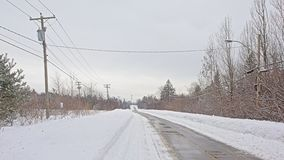 Snow covered road with electricity poles in Gatineau natural park, Quebec. Snow covered road with electricity poles and wires and bare trees on a cold grey stock image
