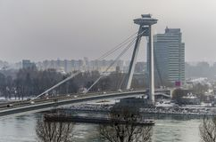 Snow and cold fog on the new bridge in Bratislava. The Danube crossed by the new bridge of Bratislava a day of fog snow and intense cold Stock Image