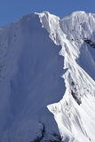 Snow cornice. A snow cornice or simply cornice is an overhanging edge of snow on a ridge or the crest of a mountain and along the sides of gullies. They form by stock image