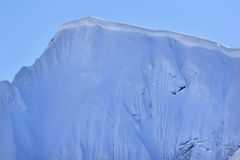 Snow cornice. A snow cornice or simply cornice is an overhanging edge of snow on a ridge or the crest of a mountain and along the sides of gullies. Cornices are royalty free stock photo