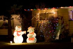 Snow Couple. A snowman and snowwoman decorate the front lawn of a home during the holiday season royalty free stock image