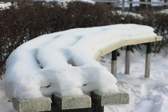 Snow cover. On the bench in the park. bokeh royalty free stock photo