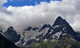 Snow cover and mountain peaks in the white clouds. Dombay the Republic of Karachay-Cherkessia in the North Caucasus, Russia. Photo taken on: July 26 Friday Stock Image
