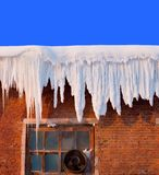 Snow cover on roof. Of old textile fabric with icicles, deep blue sky at background royalty free stock photos