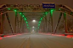Snow Coverd Bridge to North Dakota. Night Shot of a bridge over the Red River in a Blizzard. Sorlie Memorial Bridge in Grand Forks, North Dakota. Illuminated by Royalty Free Stock Photography